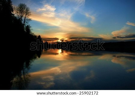 Serene sunset on water with silhouette of trees - stock photo