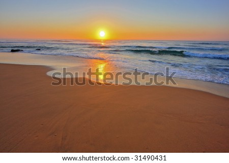 Serene wave background image, against a sunrise - stock photo