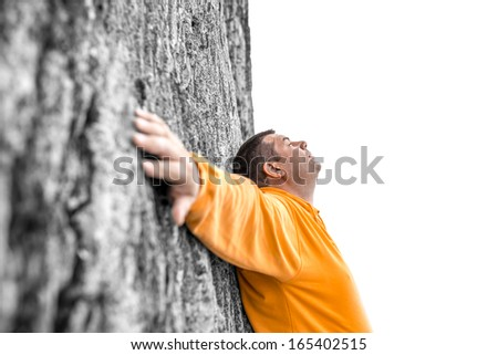 Serene young man leaning on a rock of steep climb with hands white open. Empty white space ready for your text. - stock photo