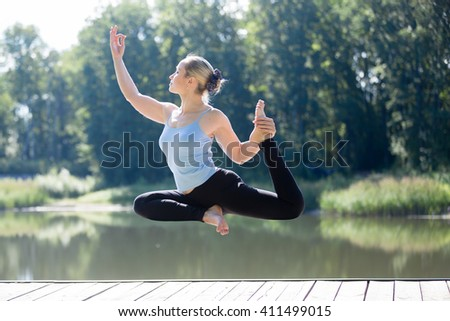 Serene young sporty beautiful woman floating in midair during yoga practice, levitating above ground in Eka Pada Rajakapotasana (One Legged Royal Pigeon Posture), working out outdoors in summer - stock photo