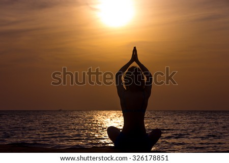 Serene young woman practicing yoga, Sitting on the sea coast at sunset or sunrise in Easy (Pleasant Pose), Sukhasana, hands above head, back view - stock photo