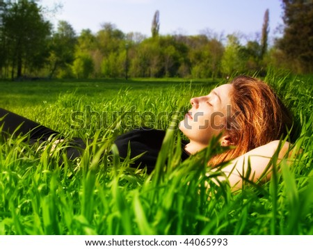 Serene young woman relaxing outdoor in fresh grass - stock photo