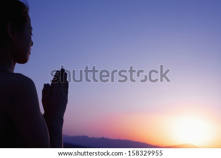 Serene young woman with hands together in prayer pose in the desert in China - stock photo