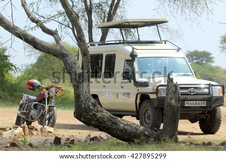 SERENGETI NATIONAL PARK, TANZANIA - JUNE 11: jeep and motorcycle parked under a tree on June 11, 2013 in Serengeti National Park. This famous and large area is visited by over 90000 tourists per year