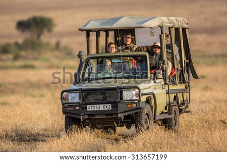 SERENGETI, TANZANIA - AUGUST 27, 2015: Tourists enjoying a game drive in the Serengeti National Park, the oldest national park in Tanzania, Africa. - stock photo