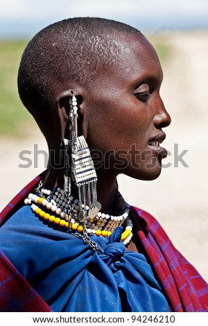 SERENGETI, TANZANIA-MARCH 16: Portrait of unidentified Maasai woman on March 16, 2010 in Serengeti, Tanzania. Maasai are a Nilotic ethnic group of semi-nomadic people located in Kenya and Tanzania. - stock photo