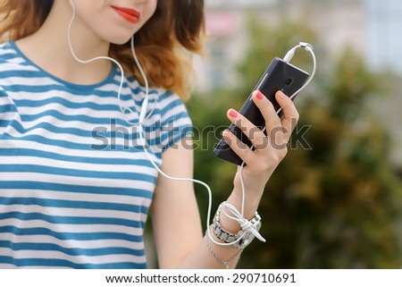 Serenity, freedom, pleasure concept. Girl in striped t-shirt is listening to music with her smartphone