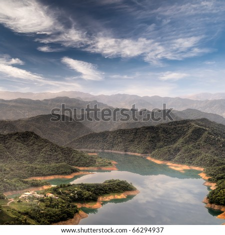 Serenity rural scenery with buildings near lake under blue sky in Taiwan, Asia. - stock photo