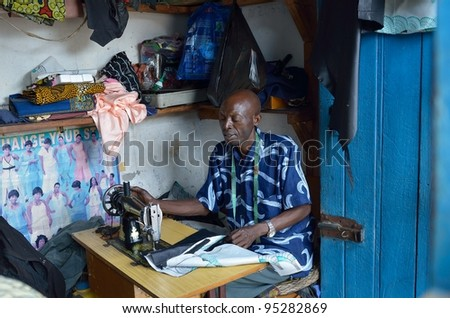 SERENJE,ZAMBIA-DECEMBER 7:an elderly tailor with his sewing machine in his small tailoring shop. Produces clothing required twenty-four hours on December 7,2011  in Serenje, Zambia. - stock photo