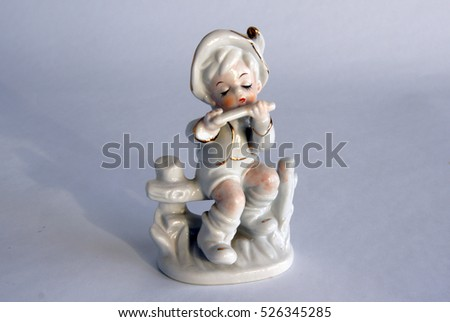 serial porcelain figurine of a boy playing a flute from the decor store - The Decor Store