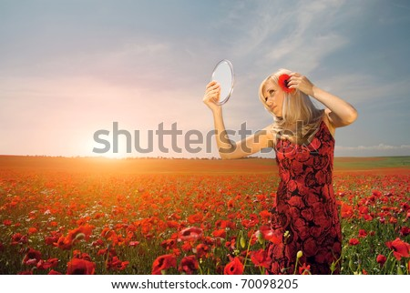 Series beautiful woman in a field of flowers looks in the mirror - stock photo