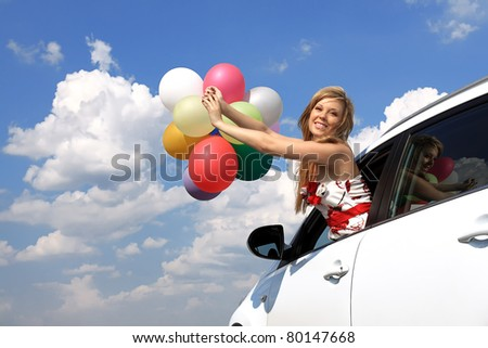 series close-up portrait of a girl in the car with colorful balloons - stock photo