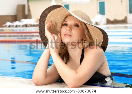 series closeup portrait the smart blonde in a hat in pool of expensive hotel - stock photo