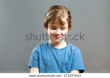 Series of a Little Boy, Expressions - Funny Giggle, looking Down - stock photo
