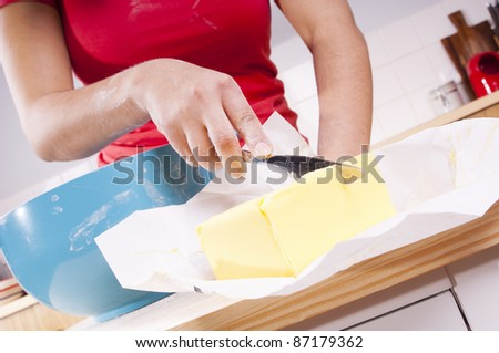 Series of a woman cooking in the kitchen with bright bowls, cutting butter - stock photo