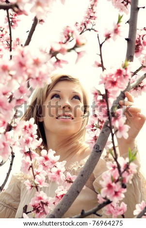 series of close-up portrait of a beautiful woman in the branches of cherry blossoms with pink flowers - stock photo