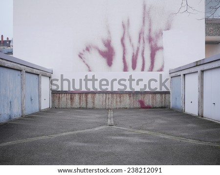 Series of garage doors in a parking area arranged on either side in two rows for parking vehicles or for use as domestic storage - stock photo