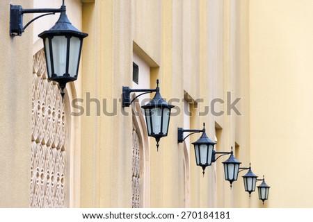 Series of lanterns on a yellow wall, Dubai, United Arab Emirates - stock photo