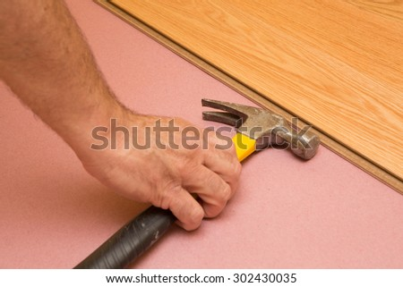 Series of shots of engineered hardwood floor being installed by a worker over pink felt paper using hand tools - stock photo