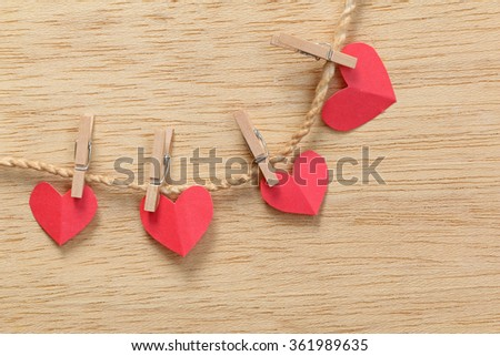 Series of Valentines Card. Four Red heart paper cut with clothes pin on wooden background, in very shallow focus. Image of Valentines day. - stock photo