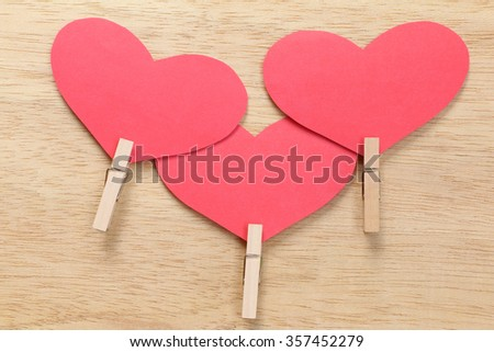 Series of Valentines Card. Red heart paper cut with clothes pin on wooden background. Image of Valentines day. - stock photo