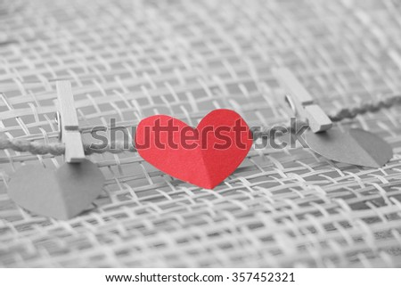 Series of Valentines Card. Red heart paper cut with clothes pin on wooden background, in very shallow focus. Image of Valentines day. Selective Color. - stock photo