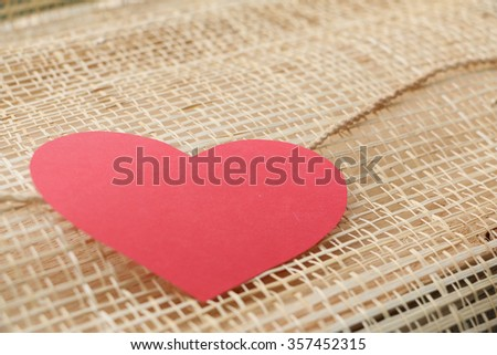 Series of Valentines Card. Red heart paper cut with on wooden weaving background, in very shallow focus. Image of Valentines day. - stock photo