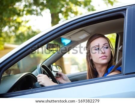Series with two teens driving in a car.  Includes lots of images with texting and looking at cel phones while in motion. - stock photo
