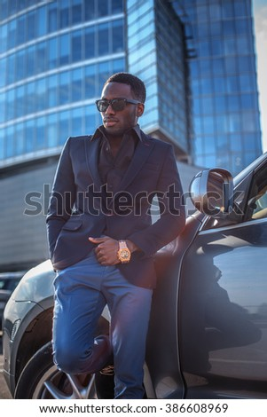 Serios blackman in sunglasses standing near the car with modern building on background