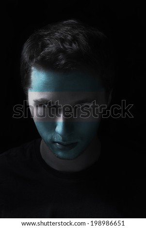 serios man face with painted flag colors of Argentina, black background