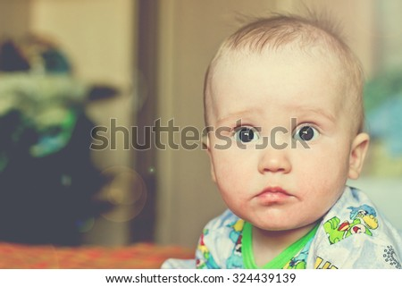 Serious adorable newborn baby boy portrait. Image with vintage filter - stock photo