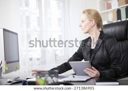 Serious Adult Blond Businesswoman Sitting at her Desk While Using Tablet and Desktop Computer Together. - stock photo