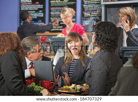 Serious adult business people meeting at indoor cafe - stock photo