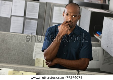 Serious African-American man with his hand on chin stands in his office cubicle - stock photo