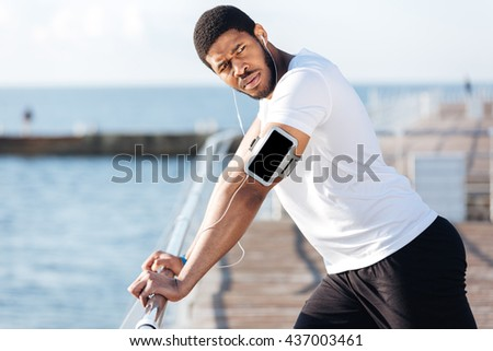 Serious african american sportsman listening to music fron blank screen smartphone on pier - stock photo