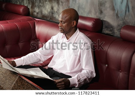 Serious african man reading paper while sitting on red leather sofa at table - stock photo
