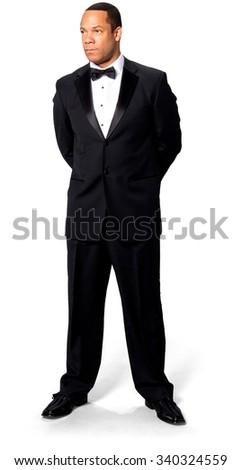 Serious African man with short black hair in evening outfit with hands behind back - Isolated