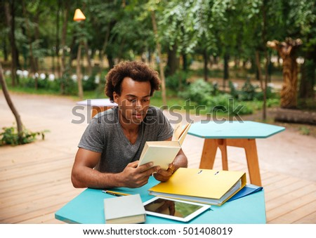 Serious african young man sitting and studying in the park