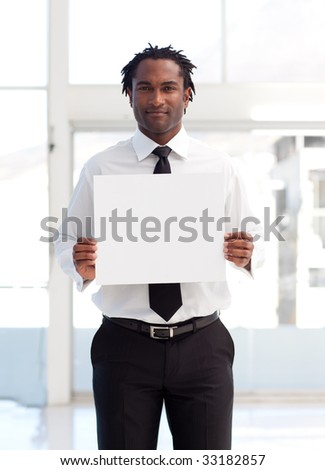 Serious Afro-American businessman holding a white card in office - stock photo