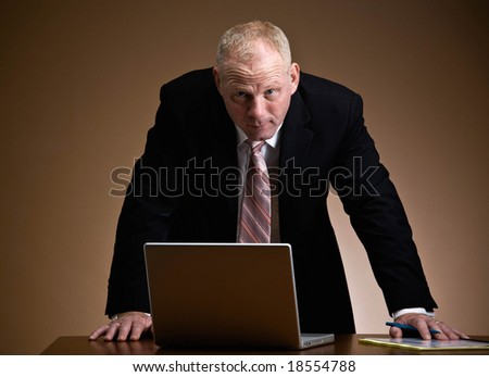 Serious, aggressive businessman leaning over laptop