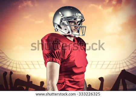 Serious American football player in red jersey looking away while holding ball against football stadium with cheering crowd