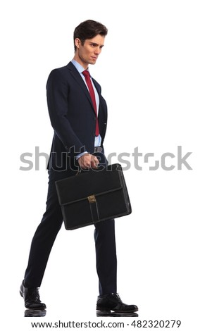 serious and confident young business man is walking forward holding a briefcase on white background