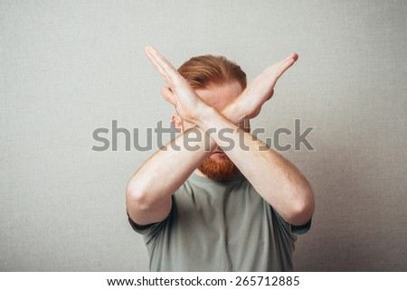 Serious and determined Young hipster red bearded Man makes an X shape with his arms and hands. stop, cross, or - stock photo