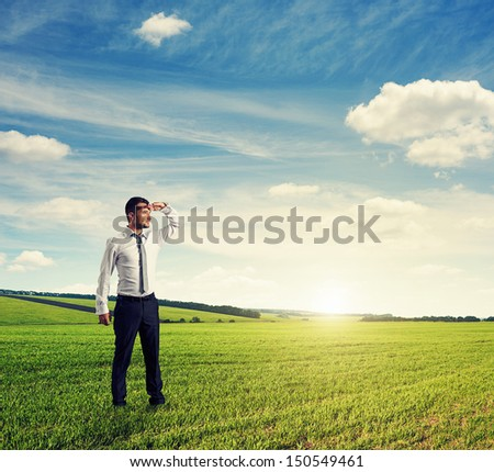 serious and thoughtful businessman standing on green field and looking forward