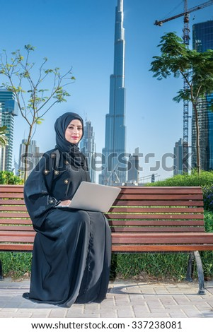 Serious Arab employee. Arab businesswomen in hijab working at a laptop on the background of skyscrapers of Dubai. The woman is dressed in a black abaya - stock photo