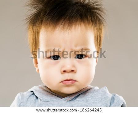 Serious asia baby boy eyebrow frown - stock photo