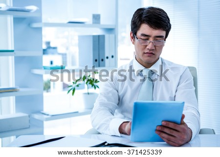 Serious asian businessman using his tablet in his office - stock photo