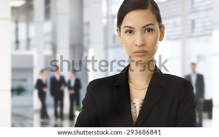 Serious attractive asian businesswoman in suit at corporate lobby. Copy space.