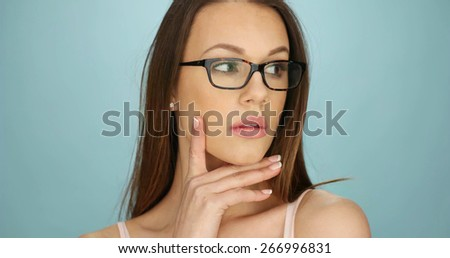 Serious attractive thoughtful young woman wearing glasses staring off to the right of the frame with her hand to her chin, closeup of her face - stock photo