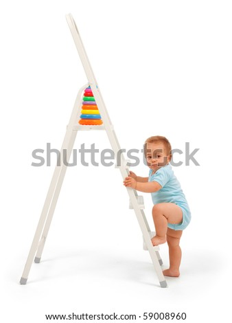 Serious baby boy wants to reach the target: walk up the ladder and get the toy - stock photo